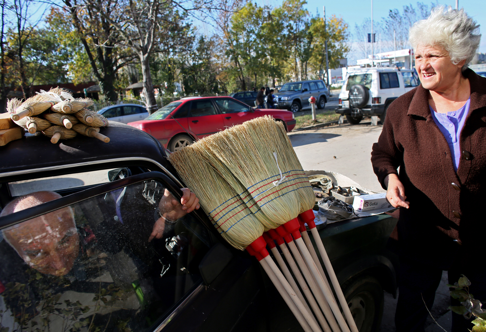 A man sells broomsticks from the roof of his car, near an outdoor market in Vidin, Bulgaria on October 18th, 2014. Many Bulgarians sell personal belongings, fruit and vegetables grown at home, or resell goods as a supplement to their primary earnings.