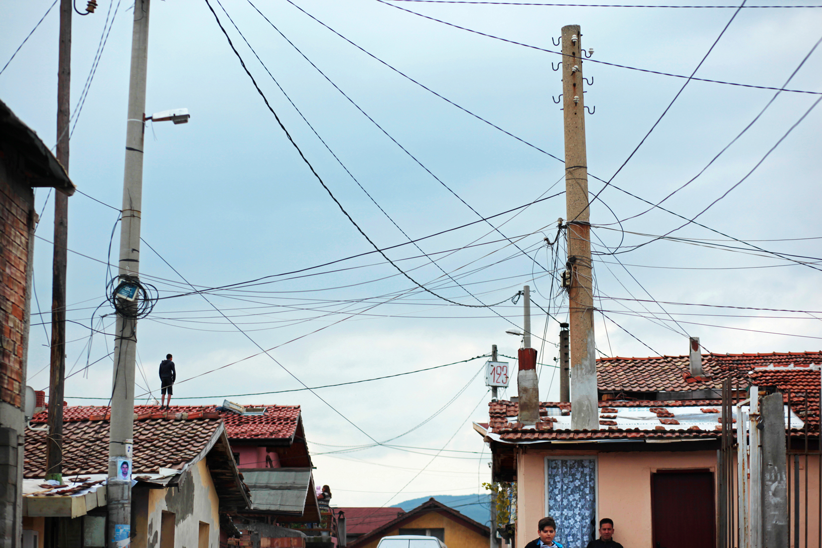 A man stands on a rooftop below a handmade electrical grid hanging over a Roma village, as people turn up to vote in October's Parliamentary elections in the nation's capital, Sofia. Today, October 5th, 2014, is also Midterm Elections day in the States - its multi-party ticket an unimaginable reality in autocratic Bulgaria pre-1989. Despite a month-long vacillation on the make-up of their political coalitions and their new prime minister - and that only 49% of the population turned up to vote today - party leaders narrowly avoided reelections, with former prime minister and leader of center-right party GERB Boyko Borisov reinstated at the post.