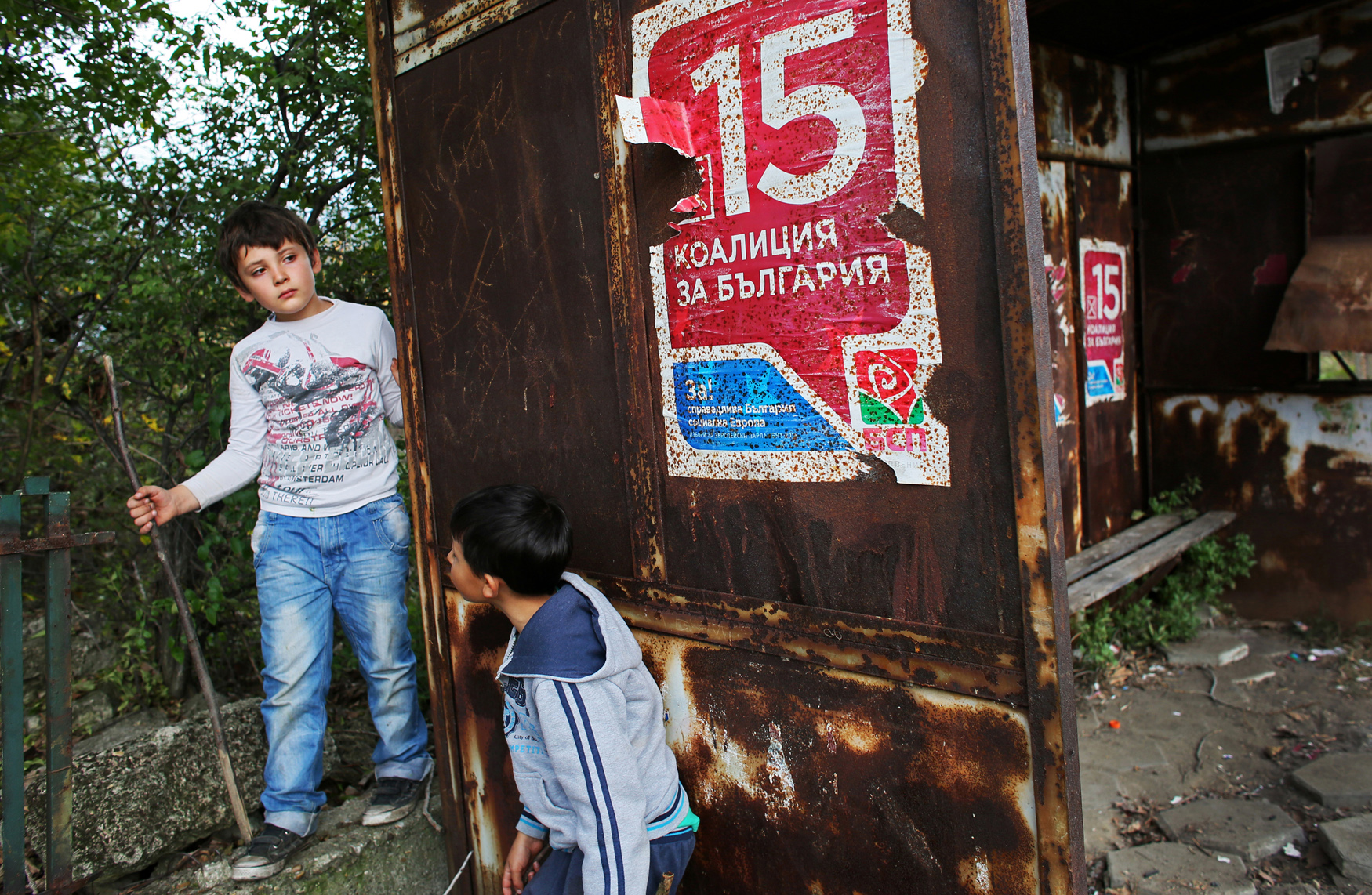 Boys rest under a poster for Bulgaria's Socialist party on a rusty bus stop on October 17th, 2014, in Rabrovo - the only village with a hospital near Kanitz, a nearly abandoned village of 6. Bulgaria has the most extreme population decline in the world — much due to post-1989 emigration, high death rates and low birth rates. There are so few people of child-bearing age in the nation that population statistics project a 30-percent decrease by 2060, from 7.2 million to just over 5 million. In other words, Bulgaria's population declines by 164 people a day, or 60,000 people a year — 60 percent of them aged over 65.