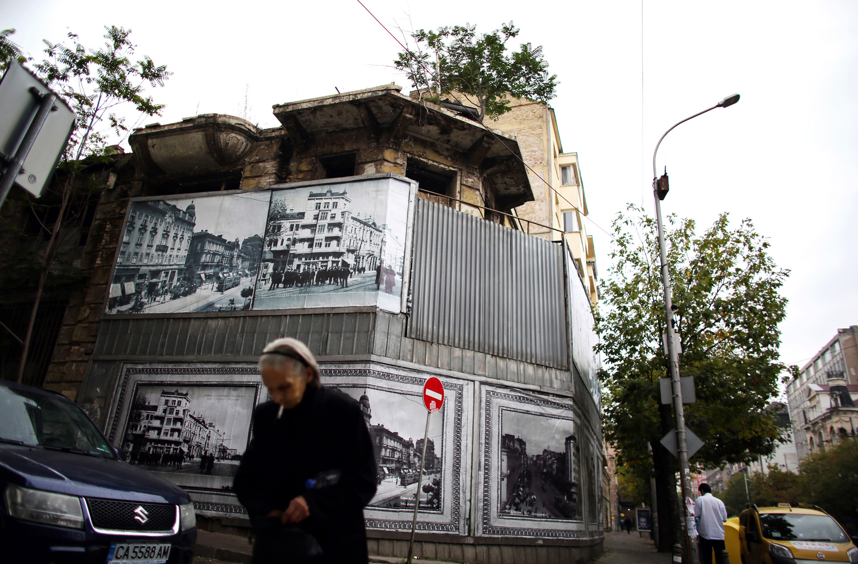 A woman walks by an abandoned building clad in street scenes of Bulgaria's capital, Sofia, on October 5th, 2014. The European Union intermittently cuts off financial aid to the country when faced with mounting evidence of misappropriated funds, meant for construction and renovation. A recent finding by Study for Democracy, a Sofia-based think tank, labeled the country's level of corruption at its highest in 15 years, across civil and political sectors alike.