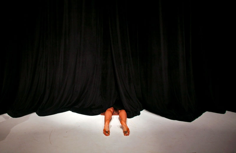 Curtains close on Julia Burrer as a dress rehearsal for the Colleen Thomas Dance program begins at the Dance Theater Workshop in Manhattan, New York on Friday, July 17, 2009. (For The New York Times)