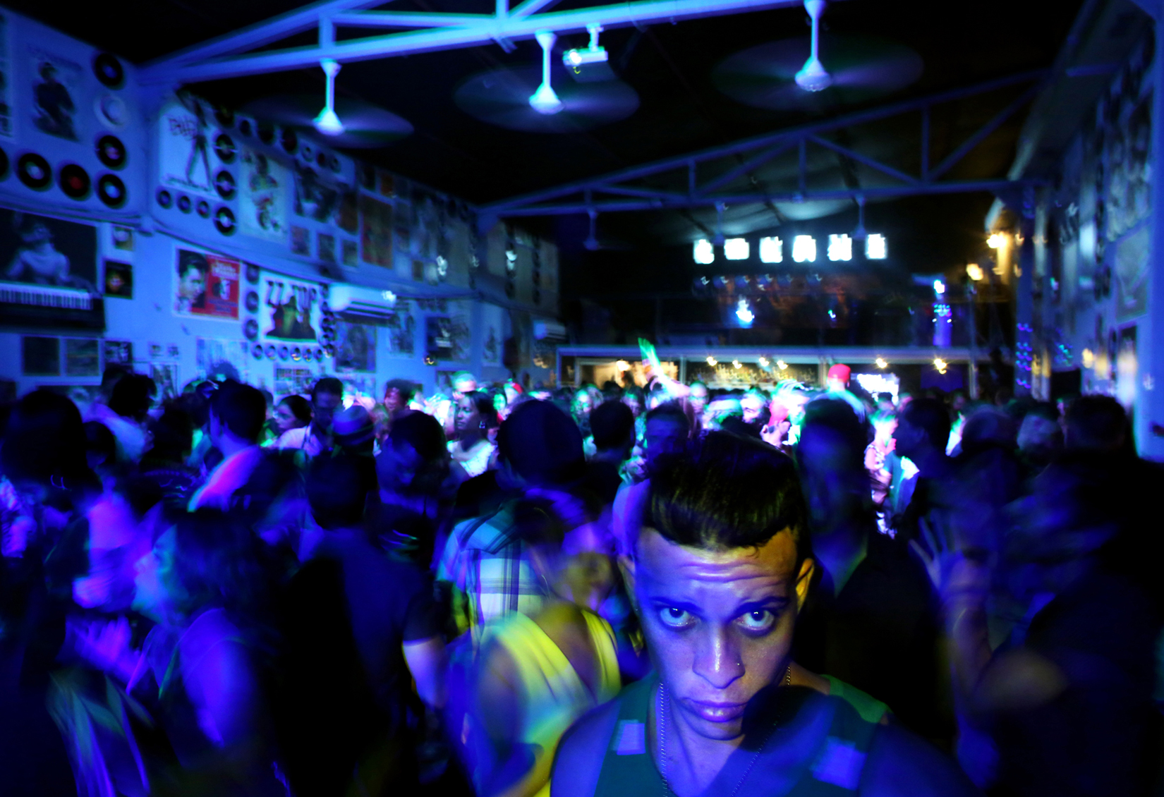 A room full of dancers mingle to the sounds of DJ Mike Polarni following a concert at Fabrica de Arte, in the Vedado neighborhood of Havana, Cuba, on April 25, 2014. Fabrica de Arte, which opened in 2014 with the backing of the Ministry of Culture, is an industrial factory turned performance space where established and unknown musicians, painters, photographers, and playwrights alike show their work. While the more open era of Raúl Castro has made it easier to toe the line of artistic self-expression, artists who cross it altogether risk losing the support of government-controlled galleries that display their works.