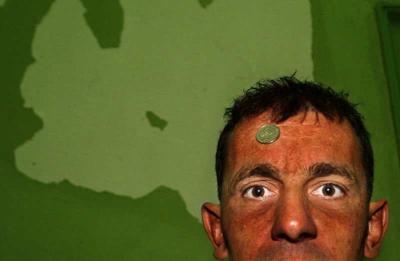 "A patient slams a Bulgarian coin on his forehead and says, ""Money controls everything. Money is why I am here. Money is why I will never get out. We have no voice here; only money speaks,"" in the psychiatry ward of a county hospital in Bulgaria on August 10, 2006."