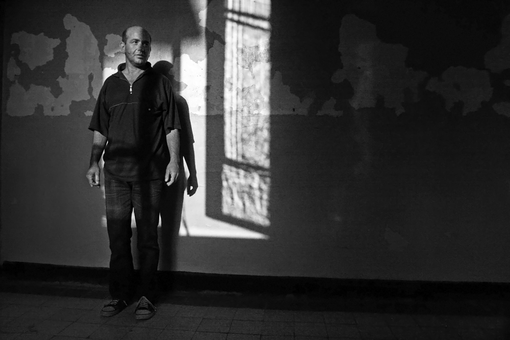 A patient hangs around, motionless, by the peeling walls against the sunset-outlined window shadow in the psychiatry ward of a county hospital in Bulgaria on August 03, 2006.