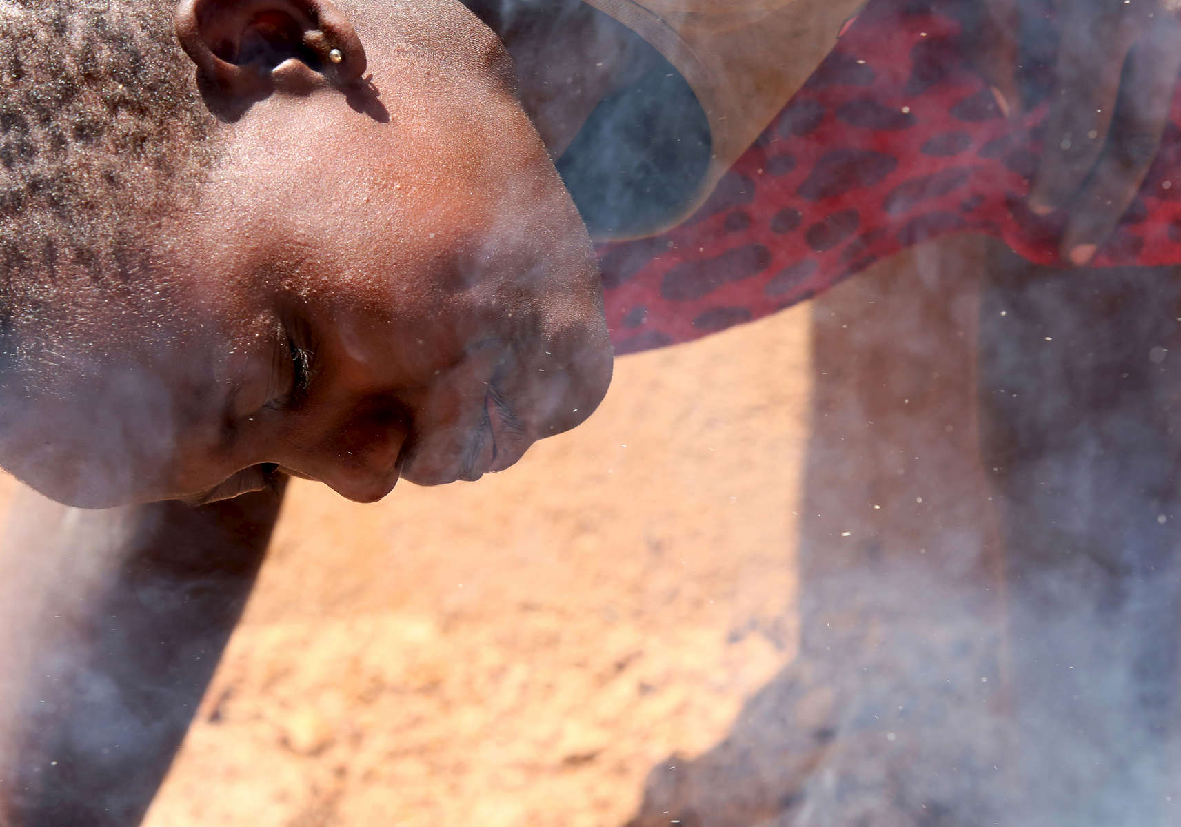 Smoke rises as twelve-year-old Sandra Gihozo blows onto a pot of beans, stoking the wooden fire beneath it in Mount Kigali village in Rwanda, on November 12, 2017. Her aunt Ruth Uwamahoro says Sandra's eyes and throat often hurt from the smoke, and that wood gathering sometimes makes her miss schoolwork.Nearly half of all Rwandans live in poverty, relying on small-scale farming for survival without gas or electricity. With so many women and children spending hours of the day foraging for wood used for cooking and light, often damaging their eyes, lungs, the forests and atmosphere, a little inventiveness helps. Enter cow and enter pig — not just as a source of food, but also the heat needed to cook it. Or more specifically, their poo — the fuel fed to a biogas digester, a tank that coverts organic waste into methane. Photographs by: Yana Paskova
