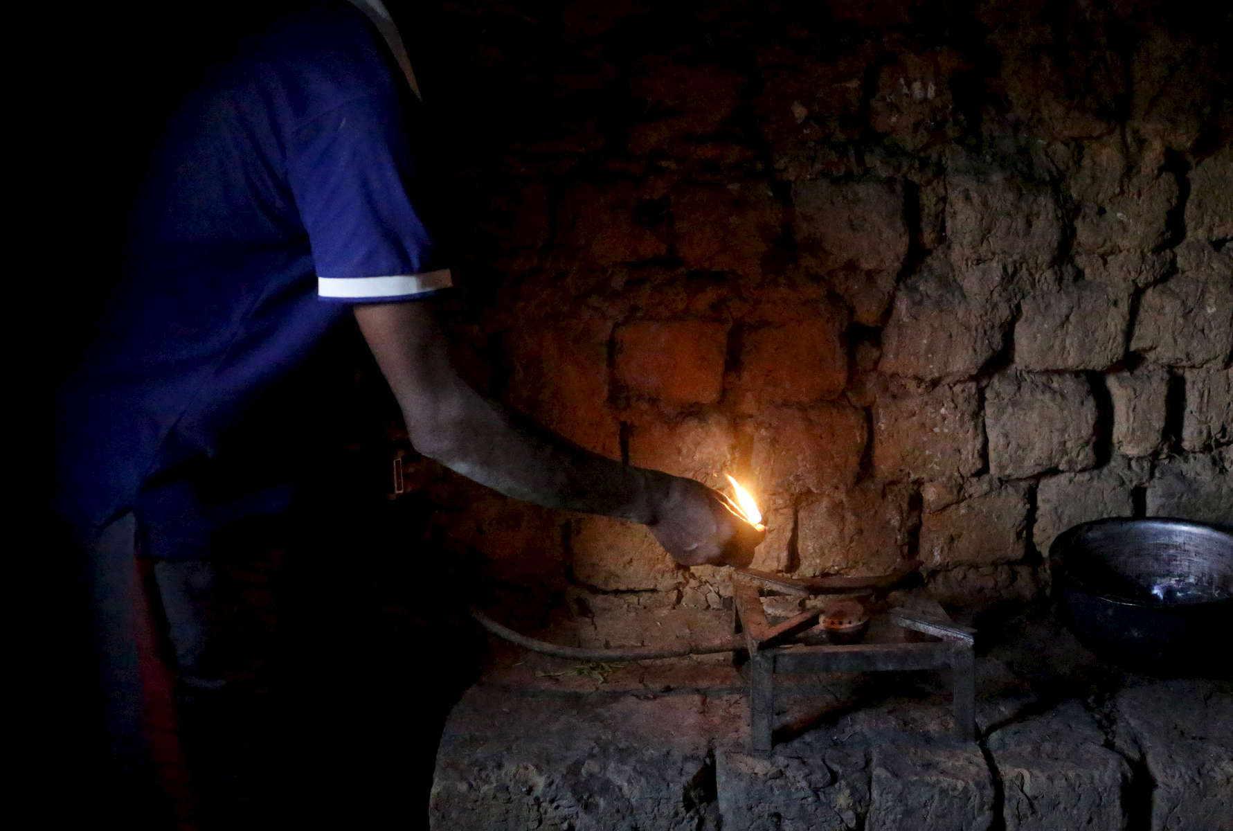 Etiene Twagirayezu, 60, lights his biogas digester in his home on November 18, 2017 in Rutabo, Rwanda. Twagirayezu says that before his digester, he'd spend up to 3 hours a day gathering 10 kilograms of wood, and saw kids get injured climbing trees and be late to school doing the same. He added he was happy his workload at home was reduced due to being able to use his cow's and pig's poo instead of wood as fuel, as well as about the resulting lessening of deforestation. Nearly half of all Rwandans live in poverty, relying on small-scale farming for survival without gas or electricity. With so many women and children spending hours of the day foraging for wood used for cooking and light, often damaging their eyes, lungs, the forests and atmosphere, a little inventiveness helps. Enter cow and enter pig — not just as a source of food, but also the heat needed to cook it. Or more specifically, their poo — the fuel fed to a biogas digester, a tank that coverts organic waste into methane. Photographs by: Yana Paskova