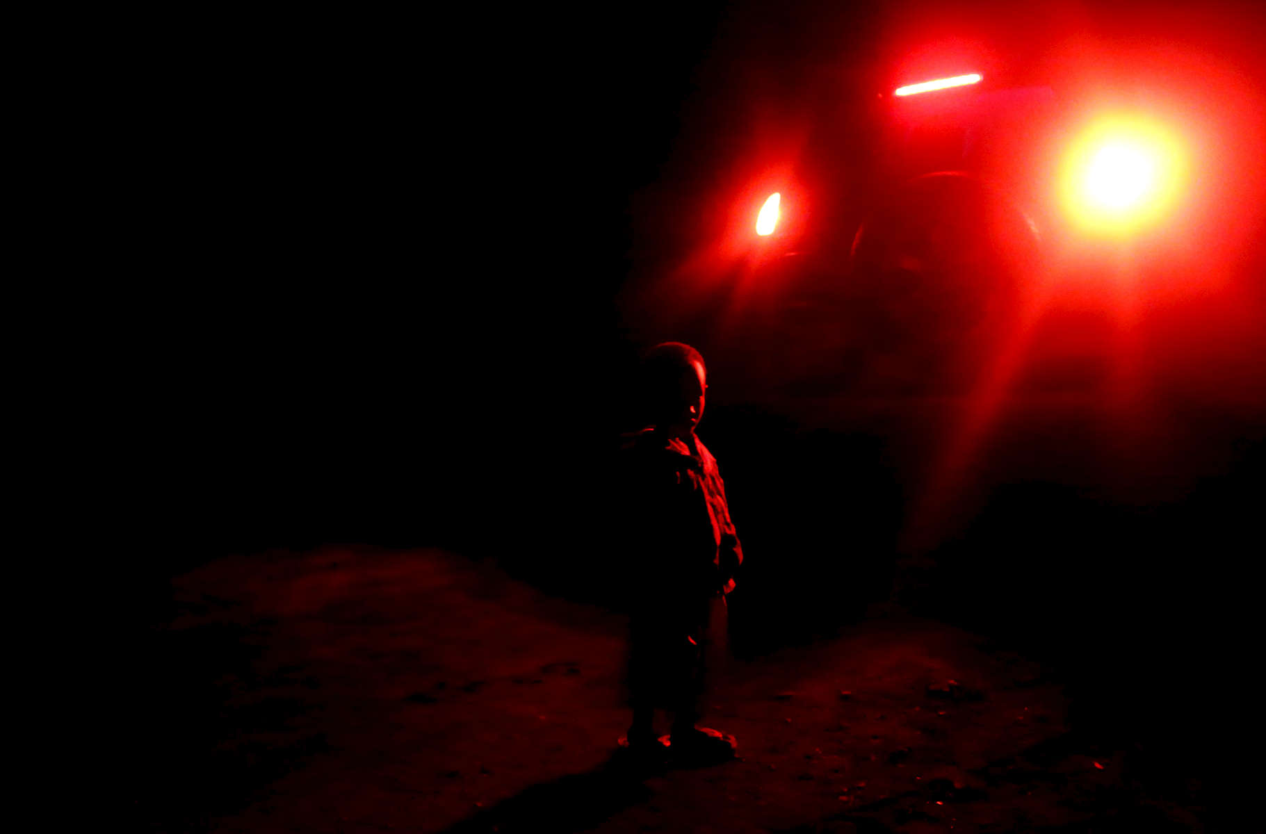 A child stands behind a car's stop lights, in near full darkness in the village of Mount Kigali, Rwanda in the evening of November 13, 2017. Nearly half of all Rwandans live in poverty, relying on small-scale farming for survival without gas or electricity. With so many women and children spending hours of the day foraging for wood used for cooking and light, often damaging their eyes, lungs, the forests and atmosphere, a little inventiveness helps. Enter cow and enter pig — not just as a source of food, but also the heat needed to cook it. Or more specifically, their poo — the fuel fed to a biogas digester, a tank that coverts organic waste into methane. Photographs by: Yana Paskova
