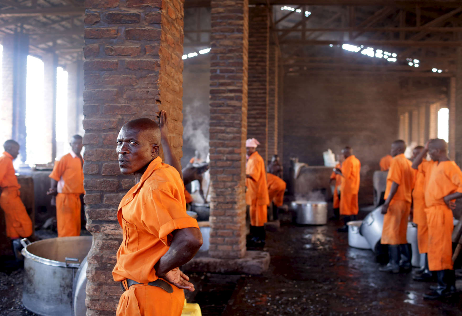 Prisoners rest in between cooking food via peat and biogas at Rwamagana Prison in Rwamagana, Rwanda, on November 18, 2017. All of Rwanda's prisons use their prisoners' waste - in addition to that of cows - to fuel their kitchens via biogas. At Rwamagana, biogas is used to cook corn, and peat cooks rice and beans. Many prisoners say they can usually tell when biogas is used due to the lack of smokey flavor in food. Nearly half of all Rwandans live in poverty, relying on small-scale farming for survival without gas or electricity. With so many women and children spending hours of the day foraging for wood used for cooking and light, often damaging their eyes, lungs, the forests and atmosphere, a little inventiveness helps. Enter cow and enter pig — not just as a source of food, but also the heat needed to cook it. Or more specifically, their poo — the fuel fed to a biogas digester, a tank that coverts organic waste into methane. Photographs by: Yana Paskova
