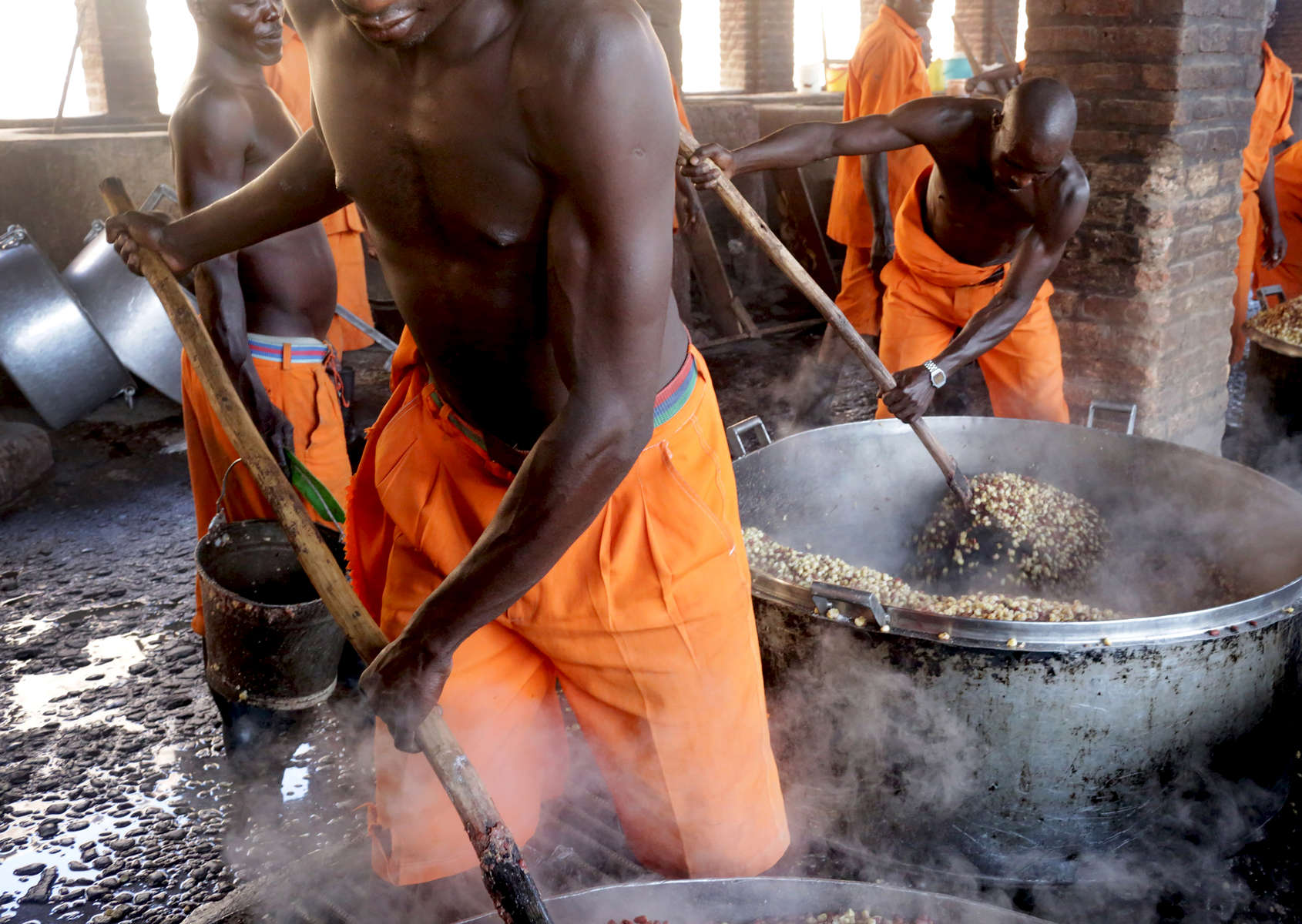 Prisoners cook corn at Rwamagana Prison in Rwamagana, Rwanda, on November 18, 2017. All of Rwanda's prisons use their prisoners' waste - in addition to that of cows - to fuel their kitchens via biogas. At Rwamagana, biogas is used to cook corn, and peat cooks rice and beans. Many prisoners say they can usually tell when biogas is used due to the lack of smokey flavor in food. Nearly half of all Rwandans live in poverty, relying on small-scale farming for survival without gas or electricity. With so many women and children spending hours of the day foraging for wood used for cooking and light, often damaging their eyes, lungs, the forests and atmosphere, a little inventiveness helps. Enter cow and enter pig — not just as a source of food, but also the heat needed to cook it. Or more specifically, their poo — the fuel fed to a biogas digester, a tank that coverts organic waste into methane. Photographs by: Yana Paskova