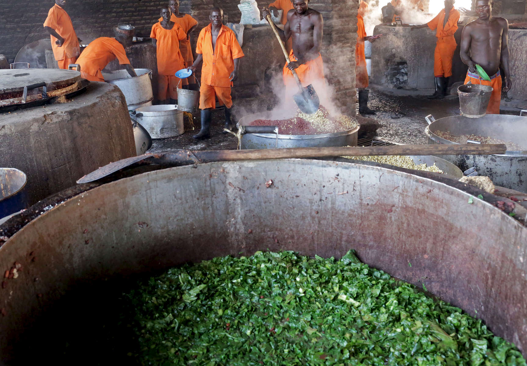 Prisoners cook food via peat and biogas at Rwamagana Prison in Rwamagana, Rwanda, on November 18, 2017. All of Rwanda's prisons use their prisoners' waste - in addition to that of cows - to fuel their kitchens via biogas. At Rwamagana, biogas is used to cook corn, and peat cooks rice and beans. Many prisoners say they can usually tell when biogas is used due to the lack of smokey flavor in food. Nearly half of all Rwandans live in poverty, relying on small-scale farming for survival without gas or electricity. With so many women and children spending hours of the day foraging for wood used for cooking and light, often damaging their eyes, lungs, the forests and atmosphere, a little inventiveness helps. Enter cow and enter pig — not just as a source of food, but also the heat needed to cook it. Or more specifically, their poo — the fuel fed to a biogas digester, a tank that coverts organic waste into methane. Photographs by: Yana Paskova