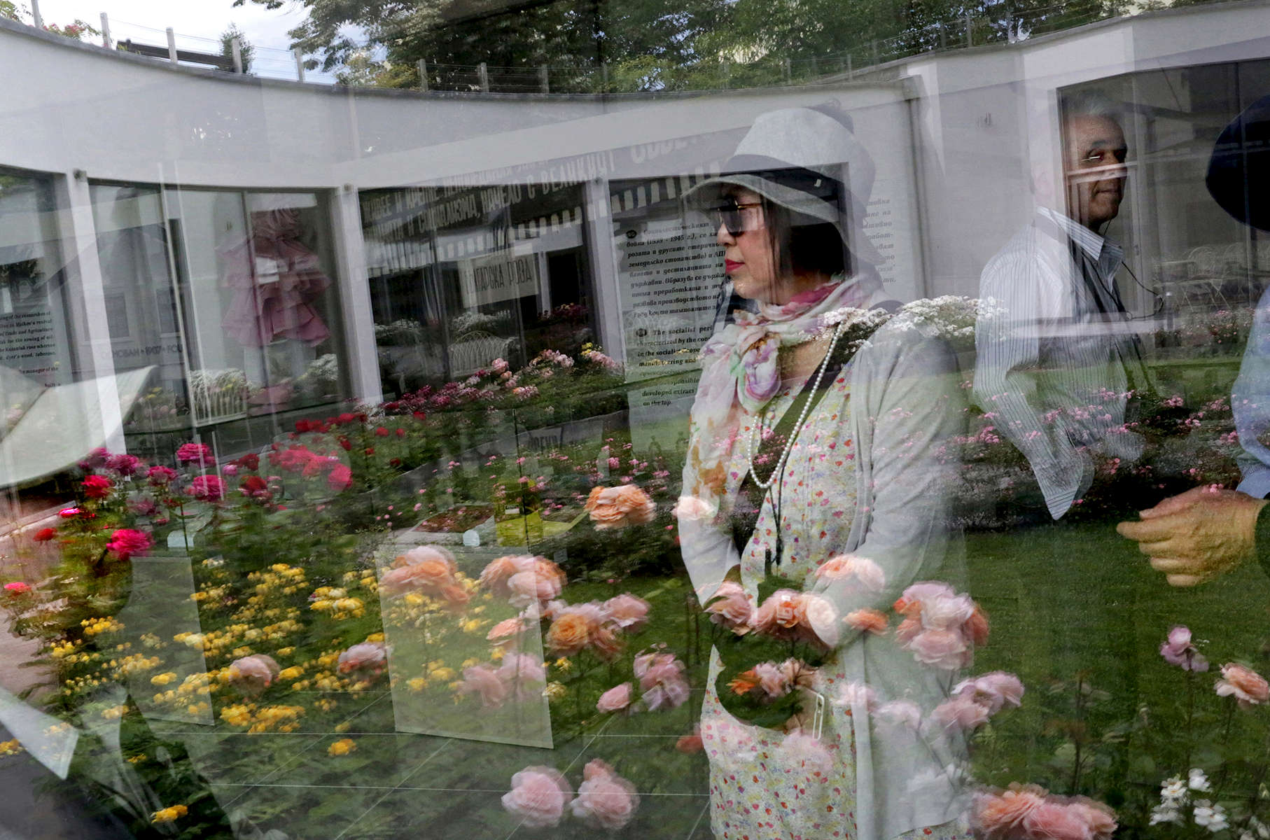 Tourists' reflections are seen on a window at the Rose Museum, which is located in the Park Rose Garden, on May 29, 2018 in Kazanlak, Bulgaria, the town regarded as the heart of Bulgaria's Rose Valley. Kazanlak boasts a Rose Festival with traditional rose-picking and distillation in the mountains, folk dances, roses ensconced in cakes, soaps, jewelry, wine and rakia (a regional 80-90 proof fruit brandy,) and even a parade in honor of its very own Rose Queen, picked from a pool of high school graduates. Photo by: Yana Paskova for National Geographic Traveler