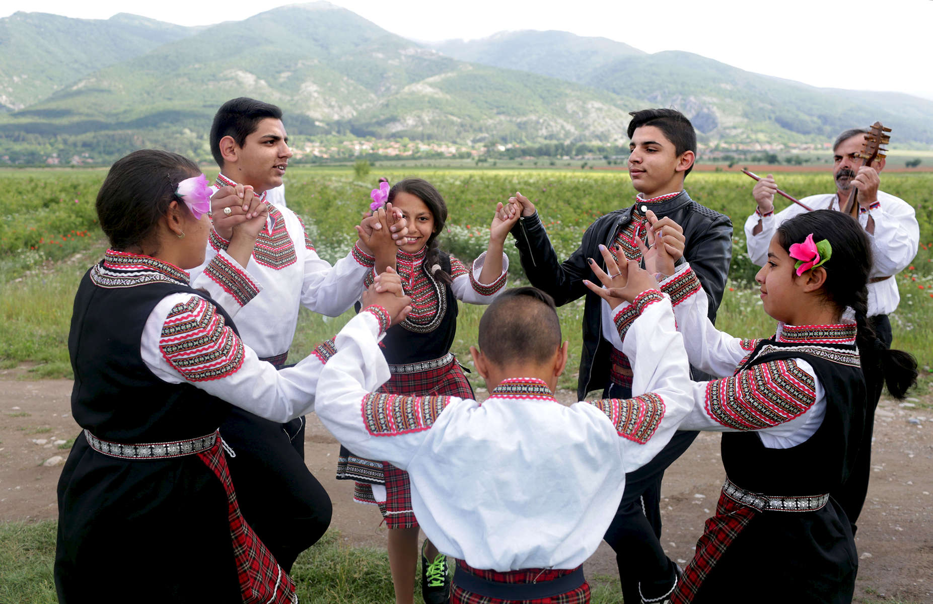 Children wearing traditional folk garb dance during a rose-picking and folk dance event organized by the municipality, in rose fields between Sheinovo and Gorno Sahrane, in Bulgaria on May 27, 2018.Photo by: Yana Paskova for National Geographic Traveler
