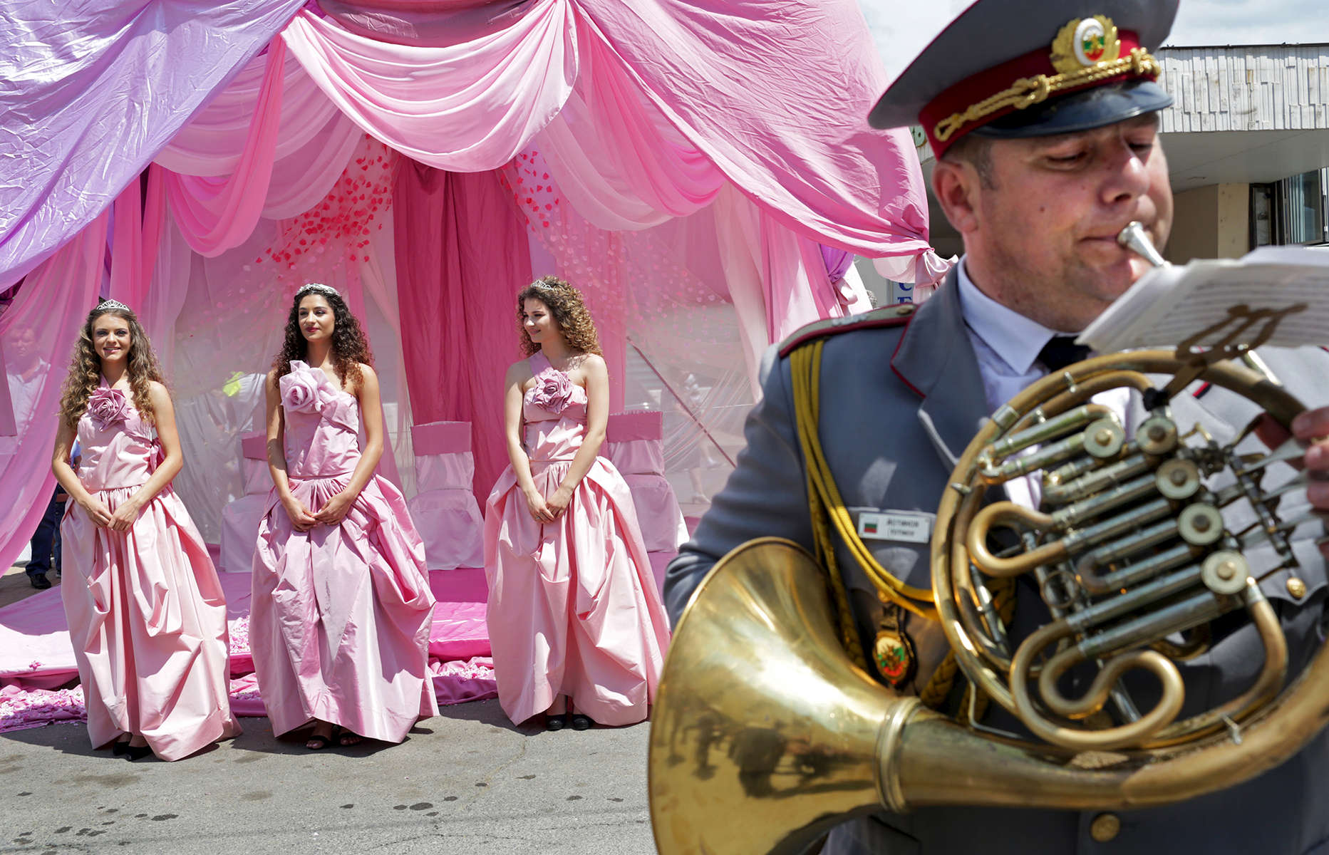 A band plans as Rose Queen Mihaela Hadzhieva, 18 (center,) poses for pictures alongside Bianka Nyagalova,18 (left,) and Elitza Slavcheva, 18 (right,) respectively second and first runners-up for Rose Queen in the Rose Festival in Kazanlak, a town situated in the Rose Valley of Bulgaria, during {quote}The Wisdom of the Rose{quote} parade, on June 03, 2018. The festival, situated in the Rose Valley of Bulgaria, celebrated 115 years in 2018. Photo by: Yana Paskova for National Geographic Traveler