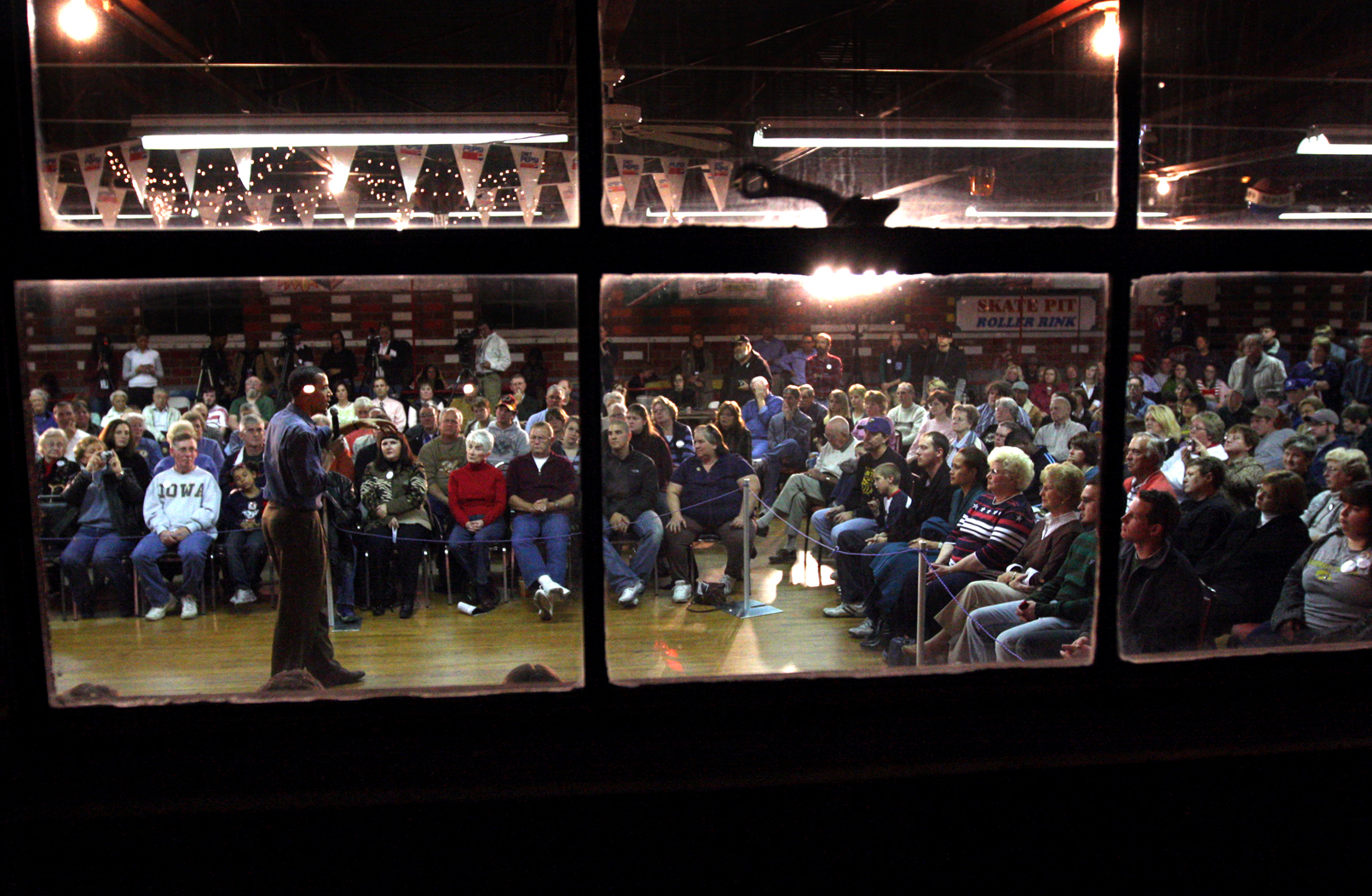 U.S. Presidential hopeful Sen. Barack Obama (D-IL), as seen through the window of a skating rink, speaks to a crowd gathered in Chariton, Iowa, on Nov. 08, 2007.