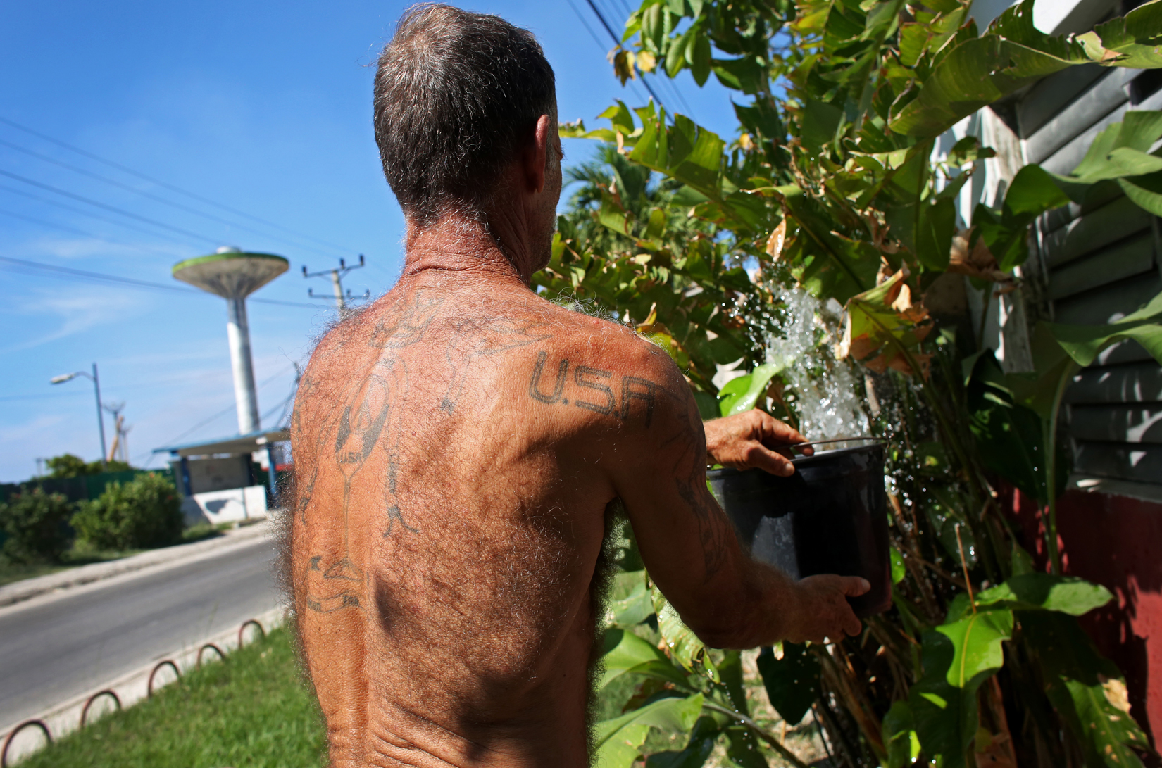 Jose Alonzo, sporting a USA tattoo, waters the plants in front of his house in the port city of Mariel, Cuba, a town whose tranquil appearance belies its important place in both the history and future of Cuban-American interaction. It is where Russians unloaded nuclear warheads in the 1962 Cuban missile crisis, and the gateway through which 125,000 Miami-bound emigres fled during the Mariel Boatlift of 1980. The town is now the site of construction of a deepwater container port and a free-trade zone, a critical ingredient for which will be the future of the U.S. embargo against Cuba, in place for more than 50 years but now under speculation of being lifted.