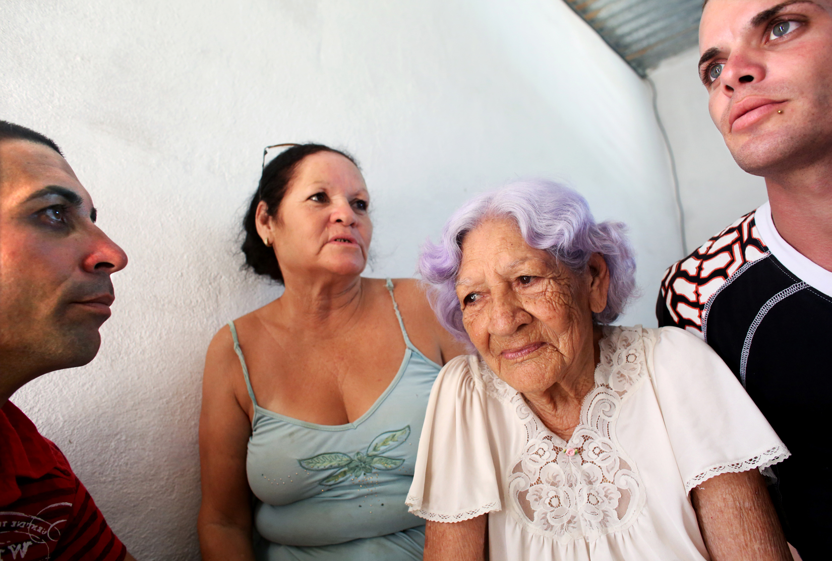 (L-R) Michael Denis Fonteto, his mother, Raizel Fonte Muñoz, grandmother Aida Muñoz, and brother, Yasiel Valdivia, spend time together in a village close to the port city of Mariel, Cuba. Yasiel and Michael's uncle was amongst those who fled toward Florida in the Mariel Boatlift exodus of 1980. The brothers say he has not since regained permission to return, separating him from his sister (their mother) and his 93-year-old mother, for 35 years. Mariel is a town whose tranquil appearance belies its important place in both the history and future of Cuban-American interaction. It is where Russians unloaded nuclear warheads in the 1962 Cuban missile crisis, and the gateway through which 125,000 Miami-bound emigres fled during the Mariel Boatlift of 1980. The town is now the site of construction of a deepwater container port and a free-trade zone, a critical ingredient for which will be the future of the U.S. embargo against Cuba, in place for more than 50 years but now under speculation of being lifted.