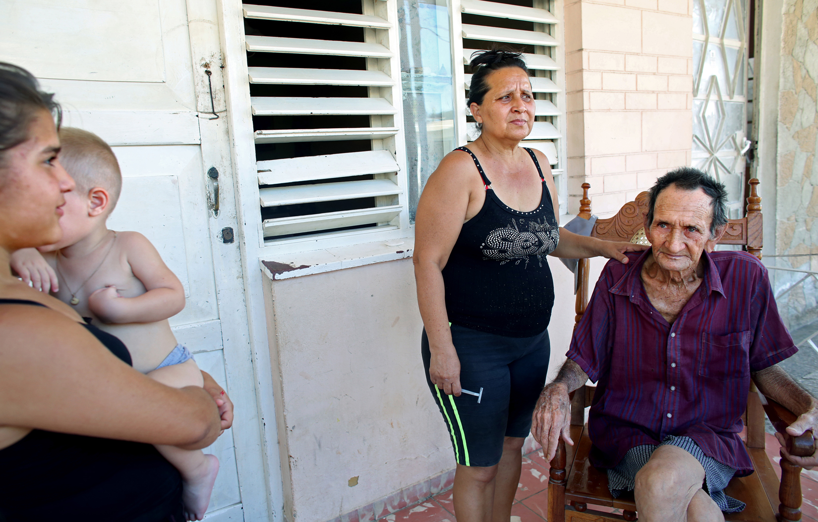 (L-R) Melani Conpagine, 13, holds her brother Mauro Peña, 1, next to the wife of a relative, Nancy Mena, 48, as she gives her father, Juaneto Mena, 82, a shave in the port city of Mariel, Cuba, a town whose tranquil appearance belies its important place in both the history and future of Cuban-American interaction. It is where Russians unloaded nuclear warheads in the 1962 Cuban missile crisis, and the gateway through which 125,000 Miami-bound emigres fled during the Mariel Boatlift of 1980. The town is now the site of construction of a deepwater container port and a free-trade zone, a critical ingredient for which will be the future of the U.S. embargo against Cuba, in place for more than 50 years but now under speculation of being lifted.