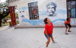 Women practice Chen-style t'ai chi ch'uan under a fresco of Cuban revolutionary philosopher and political theorist José Martí and communist revolutionary leader Che Guevara in Mariel, Cuba. Images of government idols - a famously ubiquitous sight across Cuba - fill the space that an absence of advertising leaves in printed media, billboards, and edifices.