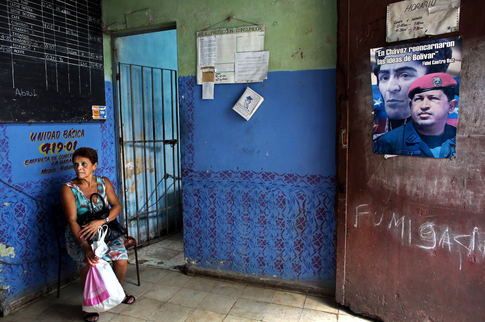 A woman waits her turn at a bodega in Havana, Cuba, near a photo of former Venezuelan President Hugo Chávez, with whom Cuba used to share a trade relationship and a distaste for American capitalism. Bodegas provide food rations - basics like rice, flour, sugar and beans, that exclude green veggies, most meat, spices or dairy (which is restricted to all but children and pregnant women) - to each Cuban citizen via the Libreta de Abastecimiento (supplies booklet,) which establishes the kind, amount and frequency of food allotted per person. The rations, which supply approximately 1/3 of Cubans' food requirements, have been kept at stable, subsidized prices since the program's inception in 1962 - as food can otherwise be forbiddingly expensive, and even at bodegas, hard to come by. This is due to a combination of inefficient farming policies, the U.S. embargo (in place since the 60s,) and the collapse of the Soviet Union in the 90s (which until then had filled the U.S.-Cuba trade vacuum with subsidies.) Food shortages, while common today, were especially sharp then, both in Bulgaria and Cuba, as the two countries tried to adjust to a non-Soviet-sponsored economy.