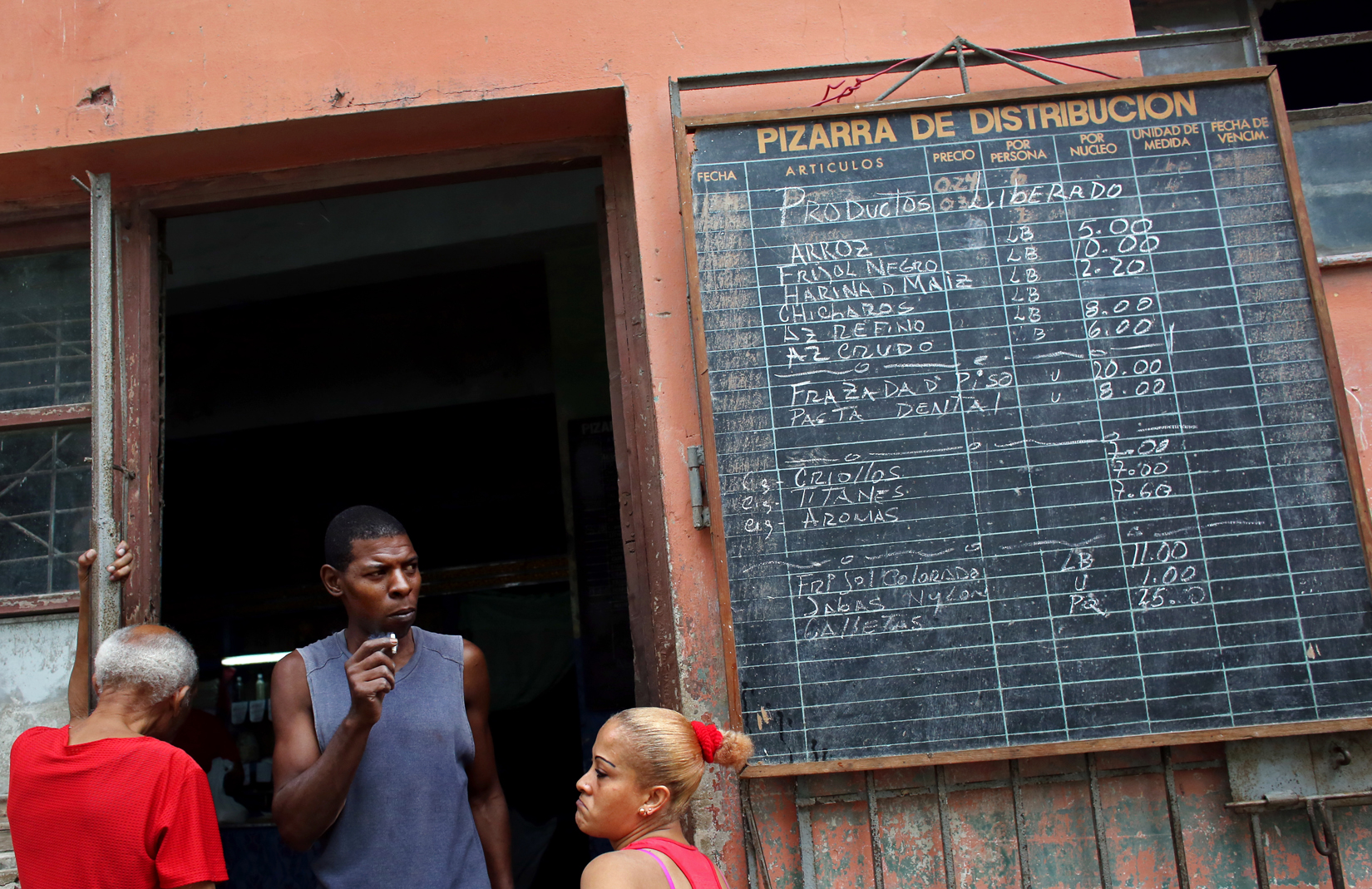 A list of available products hangs outside of a bodega (convenience store) in Havana, Cuba. Bodegas provide food rations - basics like rice, flour, sugar and beans, that exclude green veggies, most meat, spices or dairy (which is restricted to all but children and pregnant women) - to each Cuban citizen via the Libreta de Abastecimiento (supplies booklet,) which establishes the kind, amount and frequency of food allotted per person. The rations, which supply approximately 1/3 of Cubans' food requirements, have been kept at stable, subsidized prices since the program's inception in 1962 - as food can otherwise be forbiddingly expensive, and even at bodegas, hard to come by. This is due to a combination of inefficient farming policies, the U.S. embargo (in place since the 60s,) and the collapse of the Soviet Union in the 90s (which until then had filled the U.S.-Cuba trade vacuum with subsidies.) Food shortages, while common today, were especially sharp then, both in Bulgaria and Cuba, as the two countries tried to adjust to a non-Soviet-sponsored economy.