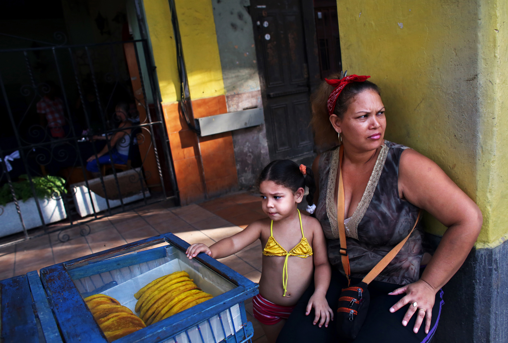 Maydelin Pérez Pérez, 38, sells empanadas with her three-year-old daughter, Lorena Sofia Reyez, in the Havana Vieja neighborhood of Havana, Cuba. Pérez is divorced, cannot afford daycare for her four children, and says her ex-husband contributes the equivalent to $1 of child support monthly. She earned less at her government job as a secretary than she does now, as one of Cuba's cuentapropistas (small business entrepreneurs, whose practice wasn't allowed in Bulgaria and most of Eastern Europe until the collapse of communism.) Since privatization was first allowed within Cuba's state-owned socialist system in the mid-70s, the requirements for those allowed to be cuentapropistas have fluctuated from restrictive to less so - the latter in the Raúl Castro era of 2008 and beyond. But a clear disincentive to private business expansion remains, however: if payroll surpasses 5 employees or a $2,000 yearly profit, taxes increase disproportionately (from 15% to 50% in case of the latter.)