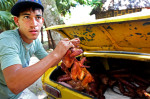 A man prepares whole grilled chicken for sale transported in the trunk of his Moskvitch, an automobile made by Russia from 1946 to 2002, before a cock-fighting event at a sports arena on April 18, 2015 in Managua, Cuba. Cock-fighting in Cuba is in the gray area of legal - state-run events such as this (non-private) functions are permitted, but not monetary betting. This is in part due to lingering bitterness over the control U.S. mafia used to exercise over casinos and prostitution in pre-revolutionary Cuba, the income from which allowed crime lords a certain level of interference in the country's political matters.