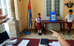 Children wearing the uniform of communist youth are directed to salute {quote}Votó!{quote} ({quote}S/he voted!{quote}) as a woman places her ballot in Cuba's Elecciones Parciales (Partial Elections) to elect delegates to the Municipal Assemblies of People's Power, the country's unicameral parliament, on April 19, 2015 in Havana, Cuba. The delegates function as district representatives for a 2.5 year term.Little Pioneers - members of the José Martí Pioneer Organization for children operated by the communist party - are often sent by polling station presidents to people's homes as a means to motivate citizens to the polls. (Voting is not mandatory, but frowned upon if not exercised.) Kids usually enter the organization in elementary school, wearing blue or red scarves - or pañoletas - to indicate the student's level, and continue until adolescence, switching to yellow and white uniforms in high school.