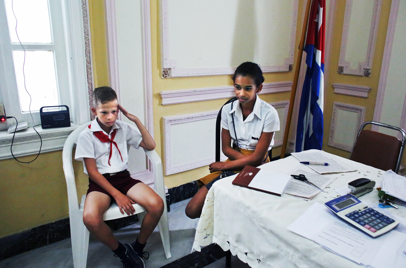 A student clad in the uniform of communist youth practices a salute given to voters as they place their ballots in Cuba's Elecciones Parciales (Partial Elections) to elect delegates from the country's single party to its unicameral parliament, this April in Havana, Cuba. Members of the José Martí Pioneer Organization for children operated by the communist party - that is quite similar to a communist youth organization in which I had to partake as a young Bulgarian student - are often sent to people's homes as a means to motivate citizens to vote. Voting is not mandatory, but heavily frowned upon if not exercised.Elementary schoolchildren wear pañoletas, or scarves as part of the organization's uniform - blue or red in color depending on their age, and switch to yellow and white uniforms in adolescence.