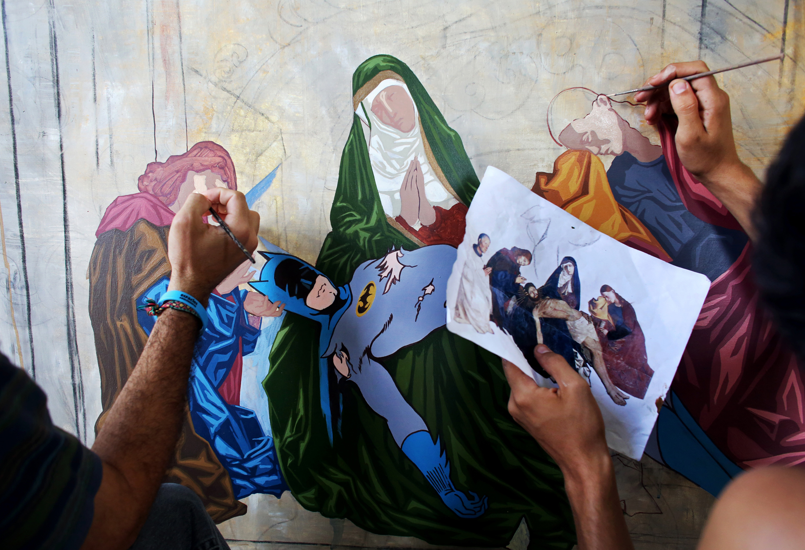 (L-R) Artists Angel León, 24, and Victor Manuel Ojeda, 24, work on nuancing a painting done by painter Eduardo Abela, 52, in Havana, Cuba, that satirically references the cult of action heroes by replacing religious figures with Western cartoon characters in copies of theological paintings. Art during the Communist years in Eastern Europe was highly sanitized - and artists who chose not to show a utopian view of the country, censored and punished. Artists in state-run Cuba as well have felt pressure to sanitize political issues and any difficulties the Cuban people may face, or omit them altogether. While the more open era of Raúl Castro has made it easier to toe the line in these areas of self-expression, artists who cross it altogether risk losing the support of government-controlled galleries that display their works.