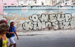 Tourists walk by graffiti of the American cartoon character Wile E. Coyote and his speech bubble {quote}Nuestro Futuro (Our Future,){quote} running by a cactus shaped to read {quote}One Up King Size,{quote} in the Havana Vieja neighborhood of Havana, Cuba. It is said to reflect the fear that a further thawing of U.S.-Cuban relations will permanently alter the cultural and economic make-up of the island. In the cartoons, Coyote repeatedly and unsuccessfully attempts to catch a fast-running ground bird, The Road Runner, his plans for capture always backfiring in injury.