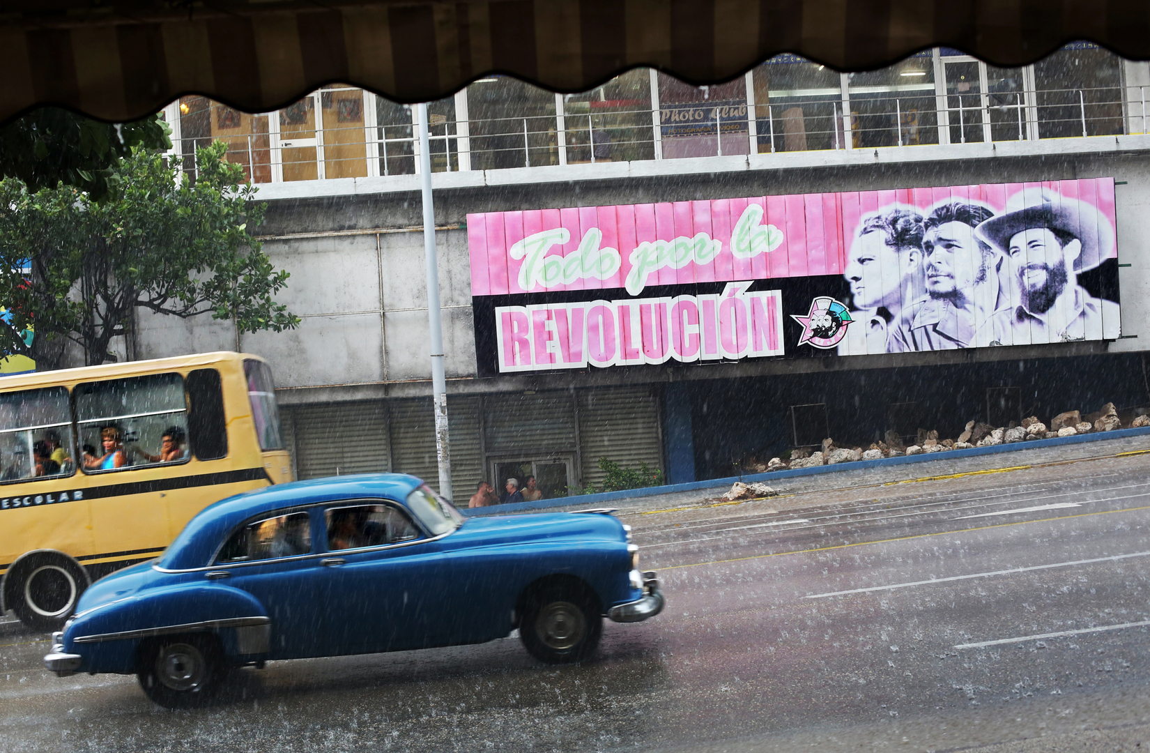 I grew up in a world almost completely clean of advertisement. It was unnecessary in pre-1989 Bulgaria: private enterprise was forbidden, eliminating retailer and manufacturer competition on production of a very limited supply of goods, that few people could afford anyway. Although entrepreneurship exists both legally and illegally on the vast government-owned landscape of Cuba, payroll taxes that increase disproportionately with the rise of annual profit discourage its expansion. Propaganda fills the space that consumerism leaves on this Havana street (a famously ubiquitous sight across the nation.) A sign for the Young Communist League (Unión de Jóvenes Comunistas,) reading {quote}Everything for the Revolution,{quote} stretches across a billboard next to the organization's motto {quote}Estudio, Trabajo, Fusil{quote} ({quote}Study, Work, Rifle,{quote}) and the likes of Cuban revolutionaries Julio Antonio Mella, Che Guevara and Camilo Cienfuegos. While the organization's membership is voluntary (and selective - based on a clean record of pro-government views,) it is highly encouraged for social and professional success.