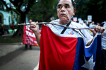 A man marching during during the 1st of May Labor Day March in Havana, Cuba, holds onto the Cuban flag on May 01, 2015. In Cuba, the day known as Día del Trabajo is a call for people to march in the streets in show of support to their local socialist government and the Cuban Revolution. Guests from many countries and social organizations worldwide are known to join the march. Participants have noted that while attendance is not mandatory, absence from the march is usually noticed and discouraged.