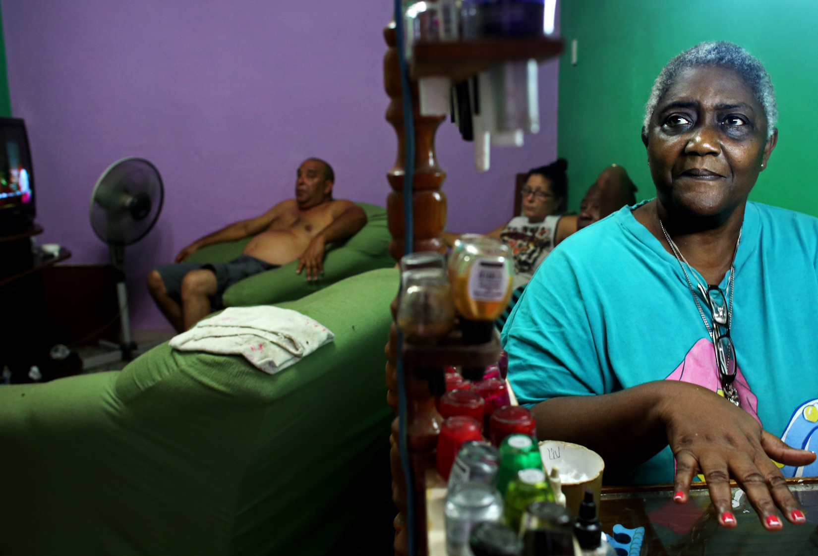 Retiree Lucilla Sulueta Cuesta, 66, gets her nails done by Liu Sanchez, 24, (not seen,) who works as a manicurist cuentaproprista (private business entrepreneur, whose practice wasn't allowed in Bulgaria and most of Eastern Europe until the collapse of communism,) in the Havana Vieja neighborhood of Havana, Cuba.   Since privatization was first allowed within Cuba's state-owned socialist system in the mid-70s, the requirements for those allowed to be cuentapropistas have fluctuated from restrictive to less so - the latter in the Raúl Castro era of 2008 and beyond. But a clear disincentive to private business expansion remains: if payroll surpasses 5 employees or a $2,000 yearly profit, taxes increase disproportionately (from 15% to 50% in case of the latter.)Cuba, a place of much recent conversation, is a country whose politics and way of life parallel much of my childhood in Bulgaria. This is 2015's continuation to my project on democracy + communism, started last year on the 25th anniversary of the fall of the Berlin Wall - the event that gave opportunity to Eastern Europeans like me to immigrate to the Western world. These are the ways in which Cuba has transported me to pre- and post-1989 Bulgaria.