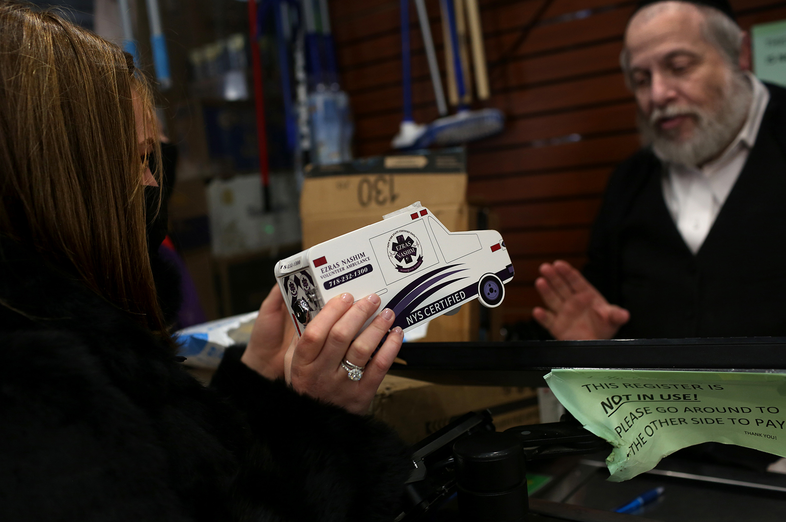 Leah Levine, 22, Ezrash Nashim COO, asks Herman Einhorn, owner of Einhorn's supermarket in Borough Park in Brooklyn, New York, to feature her organization's donations piggy bank in his store on December 06, 2020.  Einhorn, who does not feature the all-male EMT Hatzolah's piggy bank either, said he may consider it. (Photo by: Yana Paskova for The New York Times/the National Geographic Society)