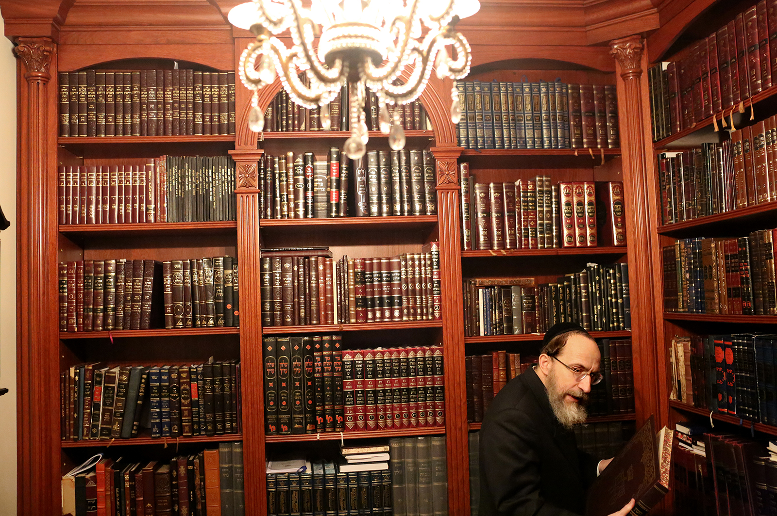 David Freier shows ancient texts on the Torah in his home in Borough Park in Brooklyn, New York on December 06, 2020. David's wife Rachel Freier and daughter Leah Levine run Ezrash Nashim, the first all-female EMT corps aimed at servicing Orthodox Jewish communities of women. (Photo by: Yana Paskova for The New York Times/the National Geographic Society)