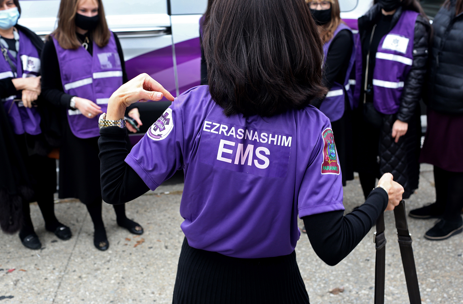 Rachel Freier (center,) founder of Ezras Nashim and a NYC Criminal Court Judge, joins other women by Gravesend Park in Brooklyn, New York to welcome their first ambulance on October 25, 2020. Ezras Nashim is the first all-female volunteer EMT corps aimed at servicing Orthodox Jewish communities of women. (Photo by: Yana Paskova for The New York Times/the National Geographic Society)