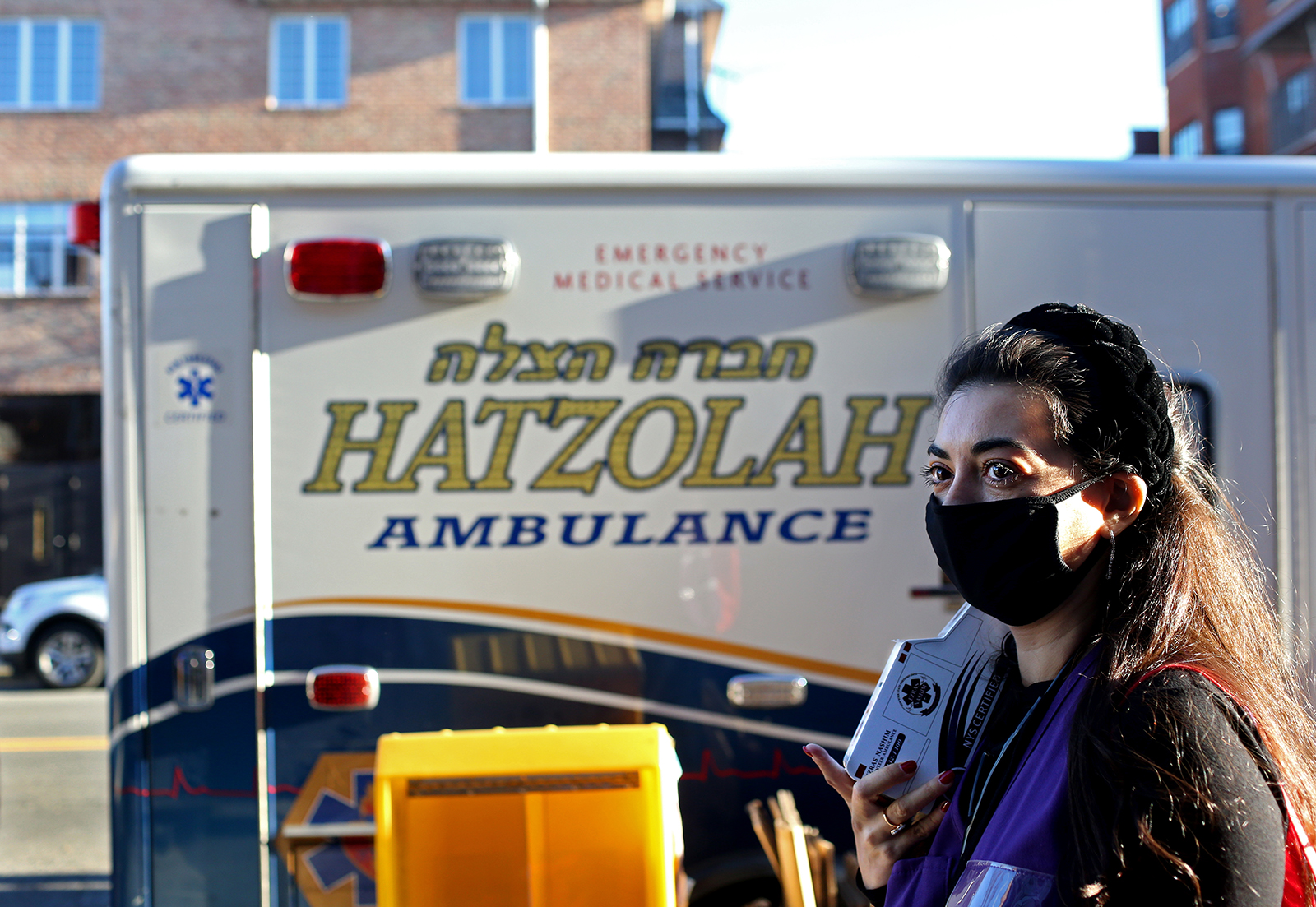 """EMT trainee Adina Sash, 34, carries an Ezras Nashim donations piggy bank around Borough Park in Brooklyn, right past the competing all-male EMTs' Hatzolah ambulance on December 06, 2020. Ezrash Nashim is the first all-female EMT corps aimed at servicing Orthodox Jewish communities of women. On the importance of Ezras Nashim, Sash says, """"When you have a community that filters education and access to information, especially about a woman's agency over her body, then it becomes even more important to equip those very women with the choice of where to turn in an emergency. Especially if the emergency is relevant to her reproductive system, having to confide in males in the community is tricky. Whereas women can help other women navigate those issues better.""""In addition to volunteering as a nurse for Ezras Nashim, in 2019 Sash ran for City Council in Brooklyn's 45th district as an Orthodox Jewish woman -- in a community that expects women to adhere to entirely different standards than male candidates, such as never showing their face in community newspaper ads, based on a religious tradition that directs men to shield their eyes from potentially improper images of women -- and says she considers herself a feminist. {quote}There needs to be more acceptance for women getting education in the Orthodox community, and the community is split on this. There is a 'If it's not broken, don't fix it' mentality because [all-male competing EMT organization] Hatzolah already exists, but there are others who understand inclusion of women leads to better care overall.{quote} On her motivations to run for office, to which she says she faced a lot of opposition from the community, she says: {quote}Making girls in the community aware that in addition to starting a family, there is importance to being part of the political process, challenges the narrative that it's a mans job to run for office.{quote}(Photo by: Yana Paskova for The New York Times/the National Geographic Society)"""