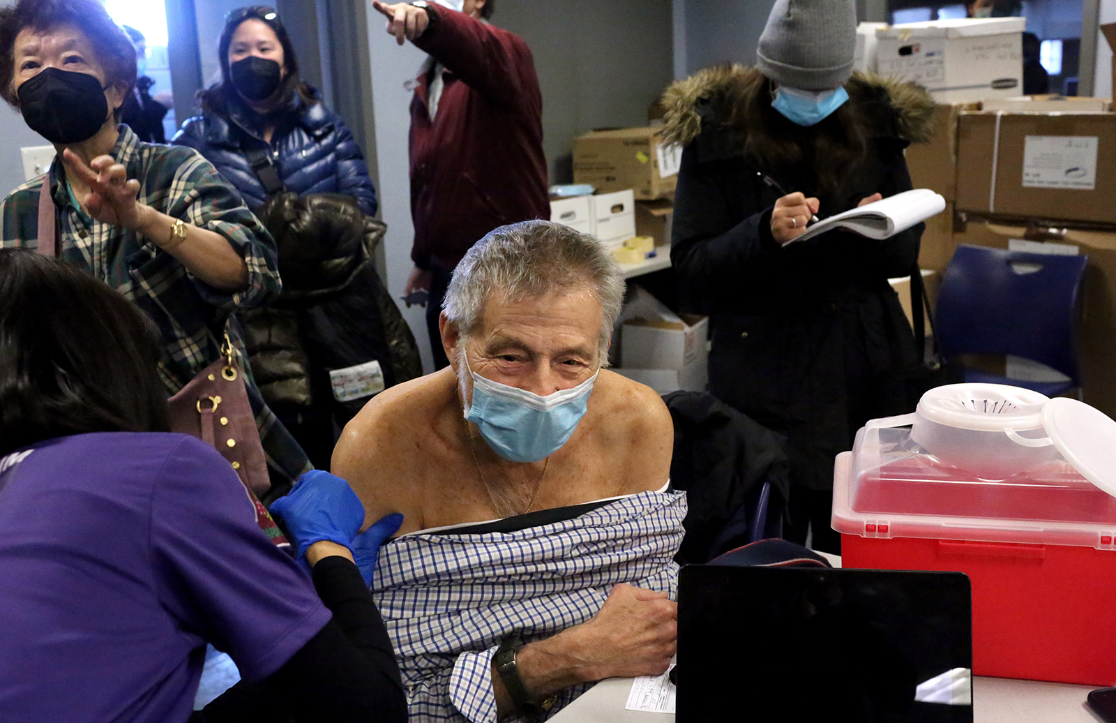 Ezras Nashim founder Rachel Freier administers a second dose of the Moderna Covid-19 vaccine to Jehuda Lindenblatt, an 83-year-old Holocaust survivor and an EMT at the competing all-male Hatzolah EMT organization, at Midwood Ambulance in Brooklyn, NY on January 24, 2021. (Photo by: Yana Paskova for The New York Times/the National Geographic Society)