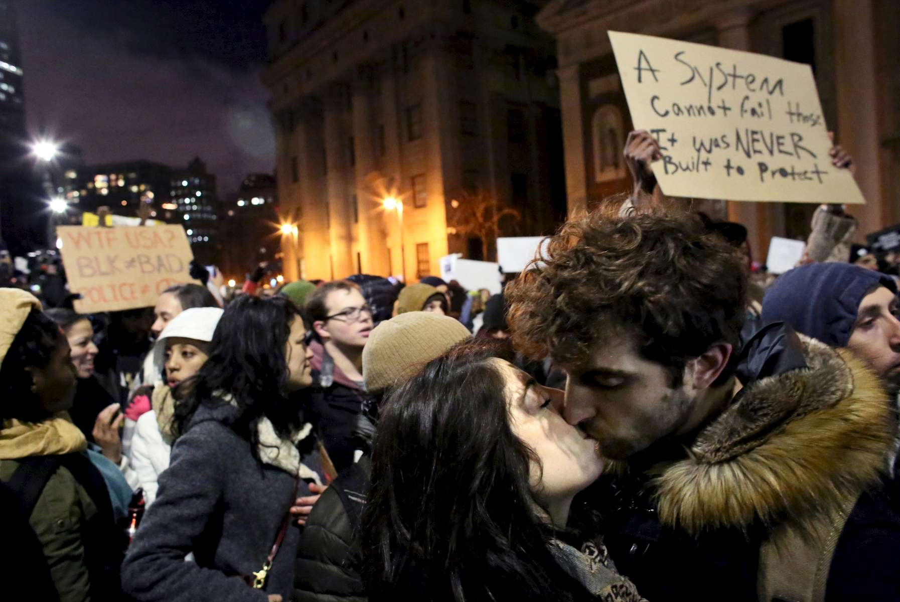 (L-R) Couple Kaitlin Ellis Fisch, 23, and Evan Leslie Jones, 25, kiss while other protesters march through 1 Police Plaza in the Millions March against police brutality deaths, starting at Washington Square Park in Manhattan, New York on December 13, 2014. Tension against police has recently escalated after the killing of several unarmed black men during routine arrests across the country.