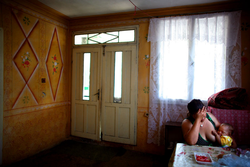 Mitka, a 15-year-old Roma mother, holds her head in her hands while breast-feeding her daughter Ivanka in Bulgaria.