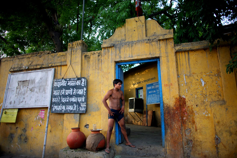An Indian man who practices traditional Kushti wrestling takes a break by the entrance of the wrestling yard on Monday, June 01, 2009 in New Delhi, India.