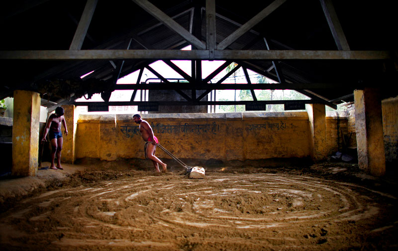 Indian men who practice traditional Kushti wrestling prepare the soil for the sport on Monday, June 01, 2009 in New Delhi, India.