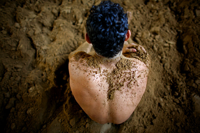 Rohit Chiller, an Indian man who practices traditional Kushti wrestling, rubs dirt all over himself before starting practice on Monday, June 01, 2009 in New Delhi, India.