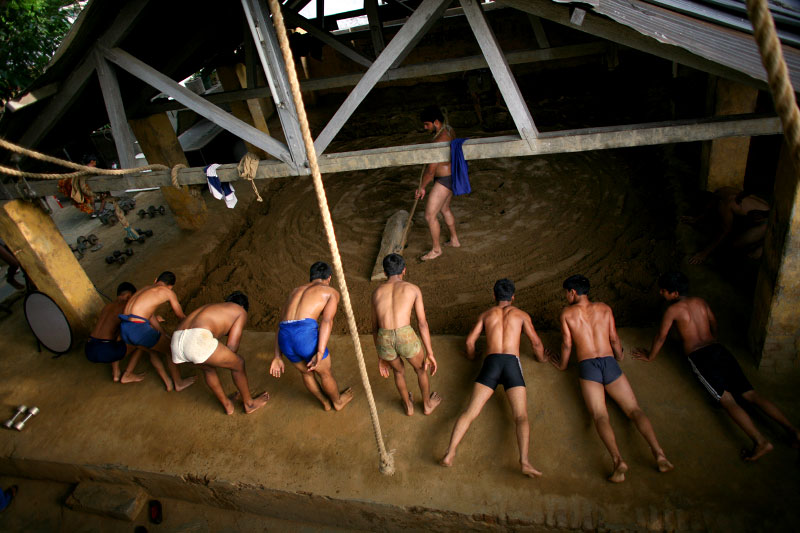 Indian men work out before practicing traditional Kushti wrestling while another prepares the soil for the sport on Monday, June 01, 2009 in New Delhi, India.