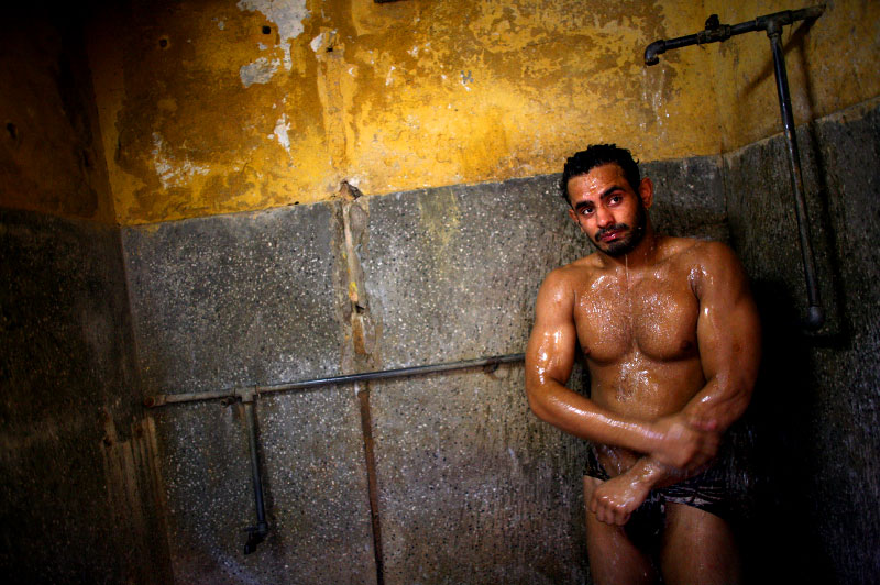 Rohit Chiller, an Indian man who practices traditional Kushti wrestling, showers after rubbing dirt all over himself during practice on Monday, June 01, 2009 in New Delhi, India.