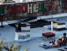 A couple soothes the wounds of lockdown by sunbathing on a Brooklyn rooftop on a May 2020 evening.