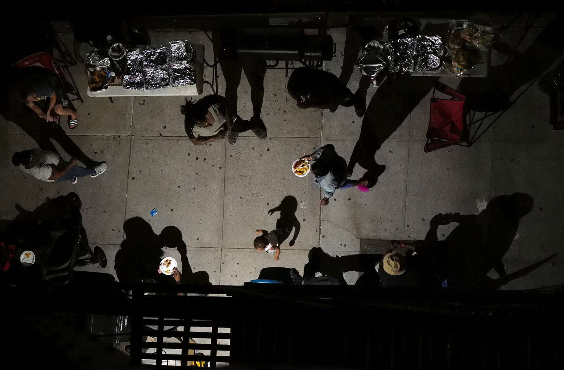 My neighbors hold a socially-distant street barbecue just below, on the sidewalk of a wide Brooklyn avenue, in August 2020, as Covid-19 ravages the United Sates.