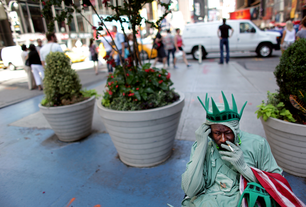 Amadou Tandia takes a smoking break from posing for tourist photos dressed as the Statue of Liberty in Times Square in Manhattan, New York on Monday, August 13, 2012.(For The New York Times)