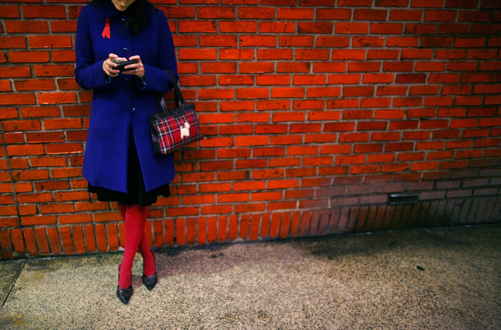 A woman checks her phone at the 49th Street station of the N train in Manhattan, New York on Sunday, December 27, 2009.(For The New York Times)