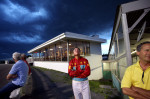 Joe Kowalski (center) checks the darkening clouds during a horse race at the Yonkers Raceway in Yonkers, New York on Tuesday, May 29, 2012.(For The New York Times)